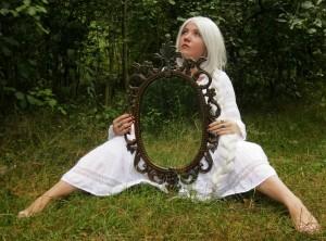 zittende vrouw in gras met spiegel